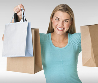 Photo of young woman holding shopping bags