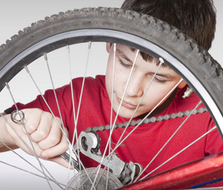 Photo of a boy repairing a bicycle