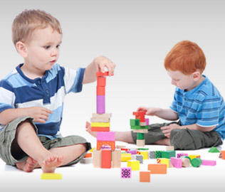 Photo of two young boys playing with building blocks